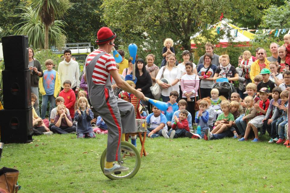 Crowds at Stoneham Park watch a juggling unicyclist